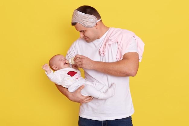 Père nourrir la petite fille avec du lait maternisé à partir de la bouteille en position debout isolé sur mur jaune