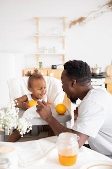 Père nourrissant sa petite fille dans la cuisine