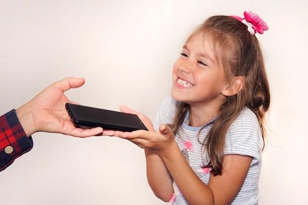 Un père offre un cadeau à sa fille pour son anniversaire. la main d'un homme passe un nouveau smartphone noir à la fille en gros plan. un enfant heureux attrape le téléphone dans ses mains.