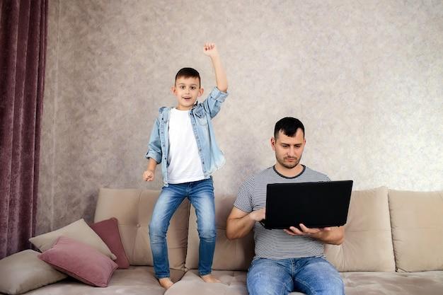 Père avec ordinateur portable travaillant pendant que l'enfant joue