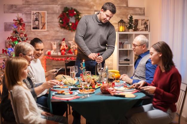 Père ouvrant une bouteille de vin au dîner de noël en famille. nourriture délicieuse.