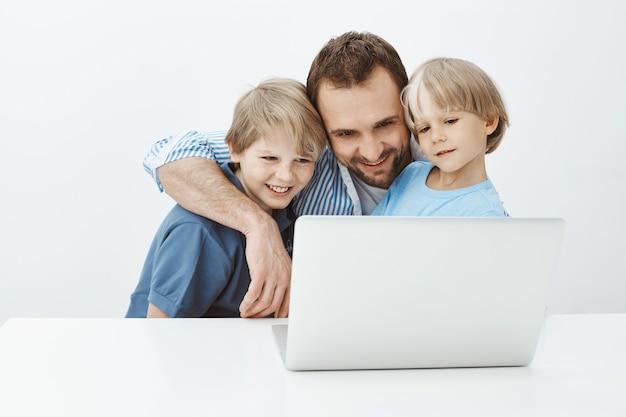 Père parlant à sa femme étreignant de charmants fils. portrait de heureux papa blond insouciant câlins garçons et souriant largement à l'écran du portable tout en parlant avec maman ou en regardant toucher des photos ensemble