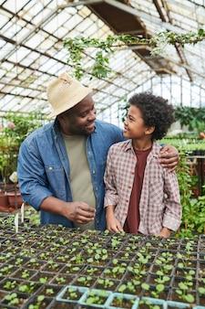 Père parlant à son fils et lui apprenant à planter pendant qu'ils travaillaient à la ferme