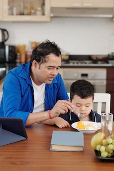 Père parlant à son fils en le nourrissant avec des tranches de fruits pour le déjeuner à la maison