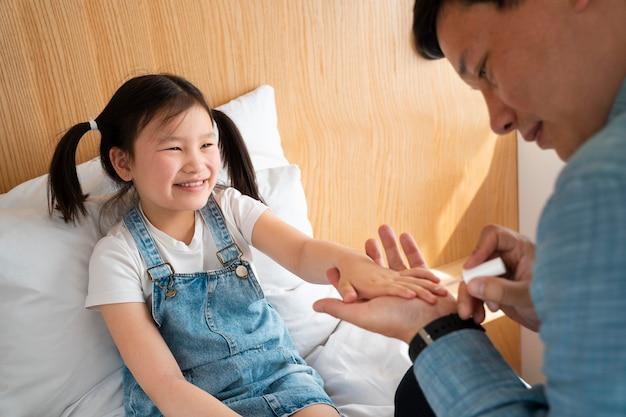 Père peignant les ongles de la fille