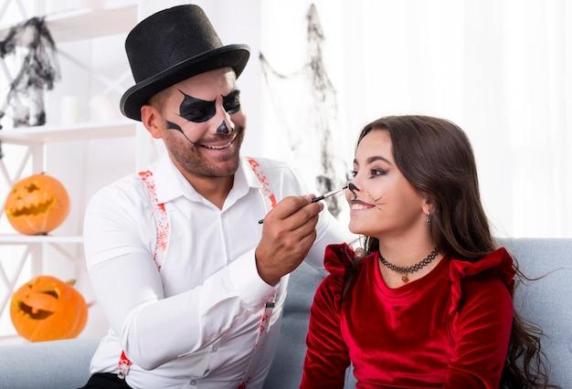 Père peignant sa fille pour halloween