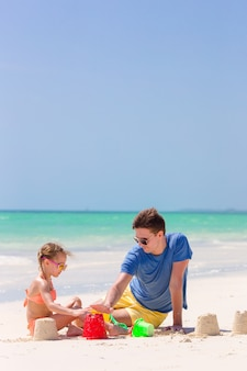 Père et petit enfant faisant un château de sable sur une plage tropicale