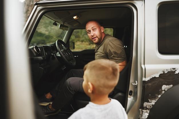 Père et petit fils debout près de la voiture en voyage sur la route