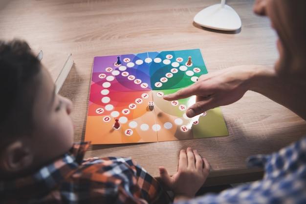 Père et petit fils jouent à un jeu de société à la maison.