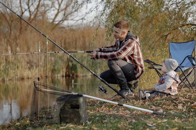 Père avec petit fils près de la rivière dans un matin de pêche