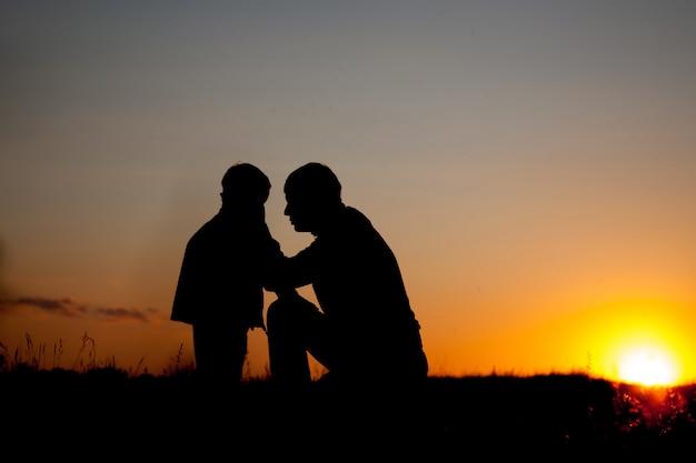 Père et petit fils - silhouettes au coucher du soleil
