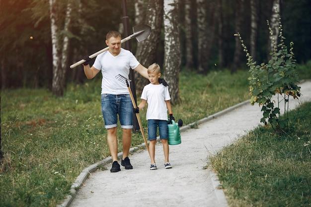 Père avec petit fils sont en train de planter un arbre dans un parc