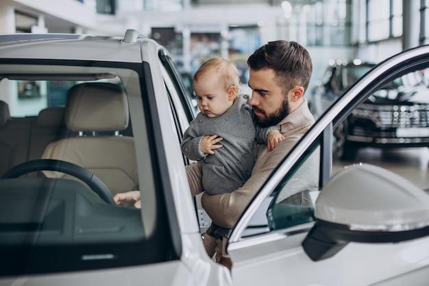 Père avec petite fille dans une salle d'exposition de voitures