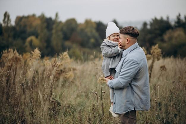 Père avec petite fille ensemble par temps d'automne s'amusant