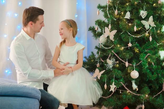 Père avec petite fille mignonne près de l'arbre de noël le soir de noël