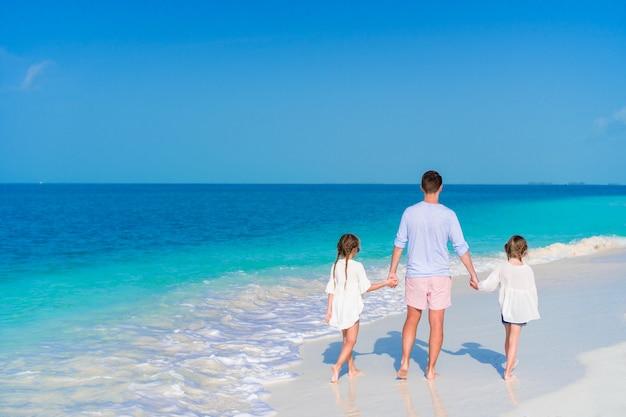 Père et petites filles marchant sur la plage de sable blanc