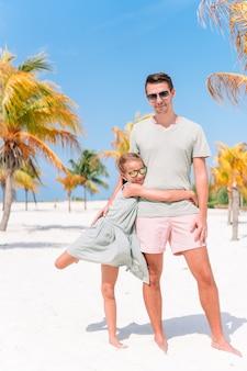 Père et petites filles s'amusent sur la plage de sable blanc