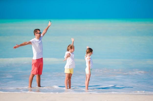 Père et petits enfants profitant des vacances tropicales à la plage. famille jouant sur la plage