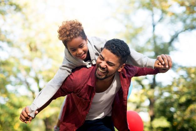 Père portant sa fille sur le dos avec les bras écartés