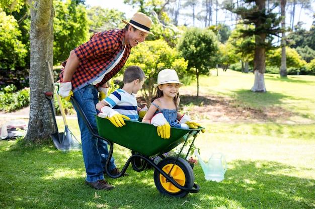 Père portant ses enfants dans une brouette
