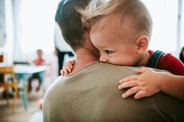 Père portant son fils dans une salle de classe