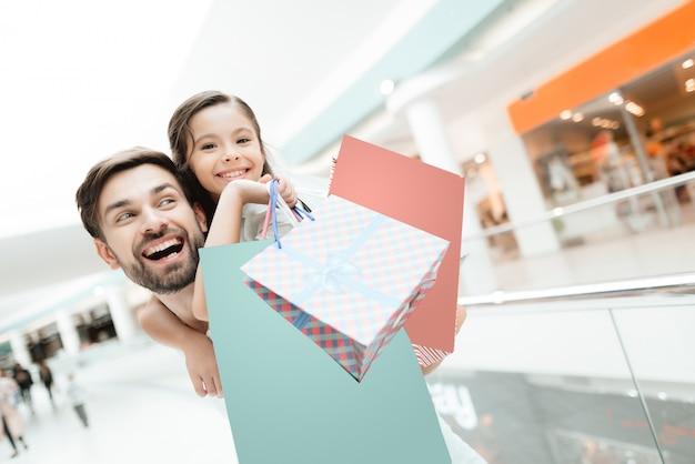 Père porte sa fille dans le centre commercial.