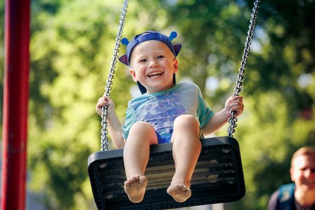 Père Poussant Son (4-5) Sur Swing In Park Photo Premium