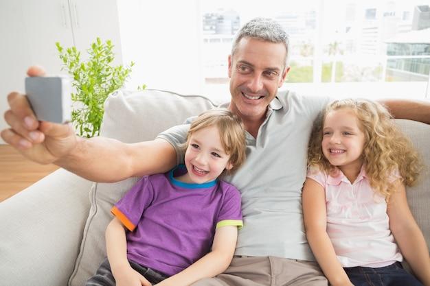 Père prenant selfie avec des enfants sur le canapé