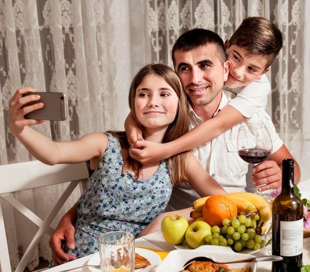 Père prenant selfie avec des enfants à table