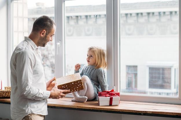 Père présent à sa petite boîte cadeau fille