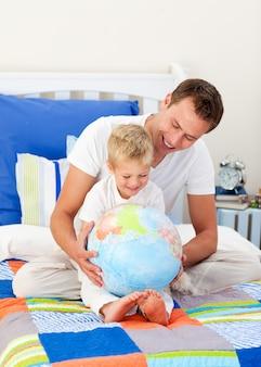 Père qui rit et son fils regardant un globe terrestre