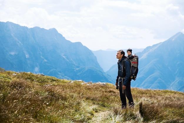 Père randonnée avec enfant dans le dos du transporteur sur le fond des montagnes