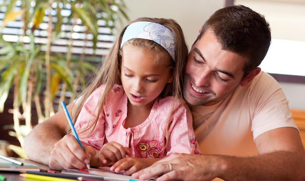 Père ravi aidant sa fille à faire ses devoirs