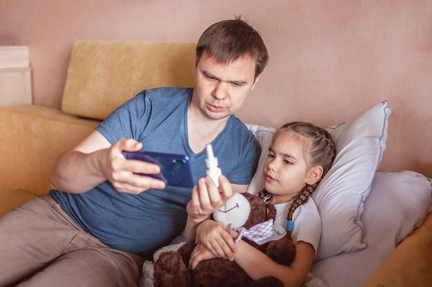 Père regardant l'écran du smartphone et consulter un médecin en ligne à la maison