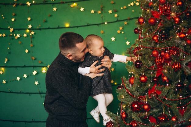 Père avec sa fille près du sapin de noël