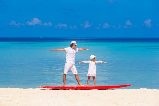 Père avec sa petite fille à la plage, pratiquant la position de surf