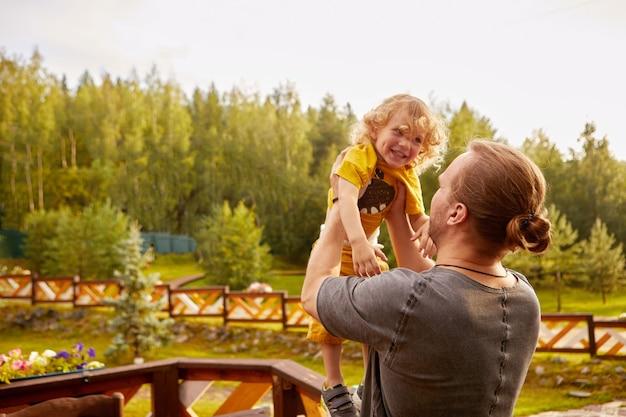 Père sans visage jouant avec son fils à la campagne