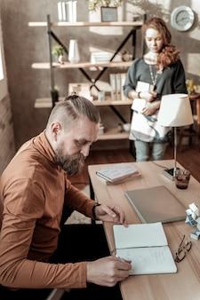 Père se sentant occupé. vue de dessus du père se sentant occupé à prendre des notes pendant que sa fille vient à lui