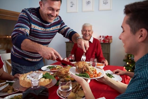 Le père sert le dîner à la veille de noël