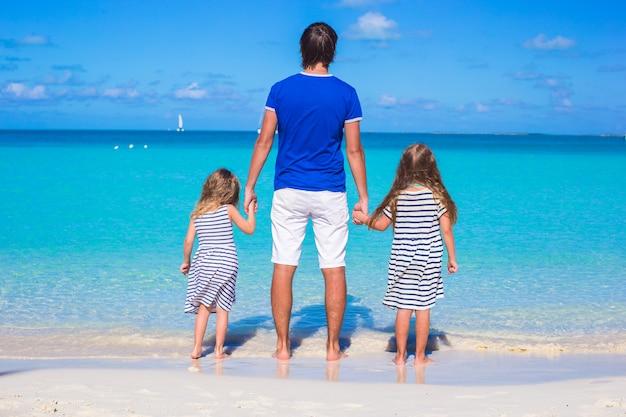 Père et ses deux enfants marchant au bord de la mer