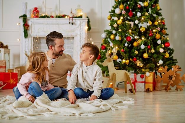 Père et ses deux petits enfants assis près de la cheminée à la veille de noël