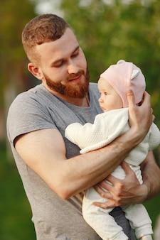 Père avec son bébé passe du temps dans un jardin d'été
