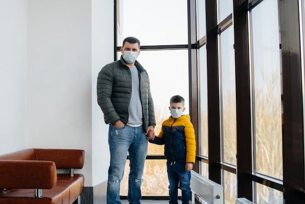 Un père avec son enfant se tient dans un masque pendant la quarantaine. pandémie, coronavirus.