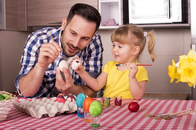 Père et son petit enfant peignant les oeufs de pâques