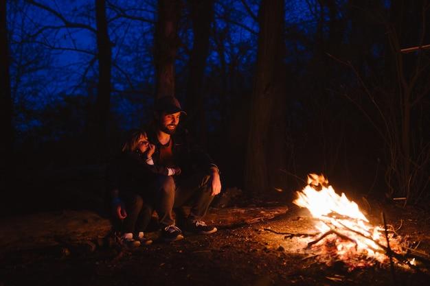 Père et son petit fils assis ensemble sur les bûches devant un feu la nuit. la randonnée en forêt. .