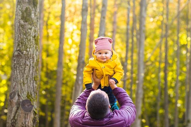Père et son petit fils s'amusant dans le parc de l'automne