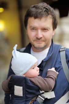 Père et son petit garçon dans un porte-bébé, portrait en plein air