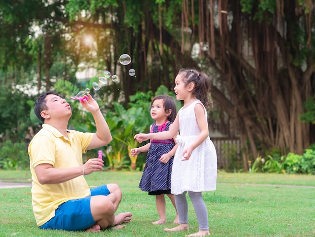 Père souffle des bulles pour deux petites filles à jouer dans le jardin.