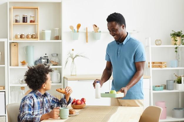 Père souriant africain a préparé le petit déjeuner, il va prendre le petit déjeuner avec son fils à la table dans la cuisine