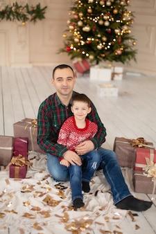 Père souriant embrasse son fils à l'arbre de noël, cadeaux entourés. bonnes vacances en famille.